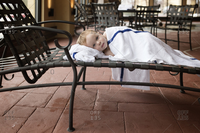 Boy wrapped in blankets on pool chair