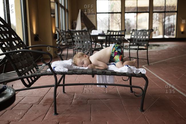 Boy asleep on indoor pool chair