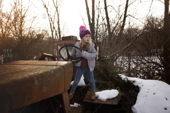 Girl standing on old tractor