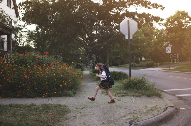 Girl walking with instrument in neighborhood