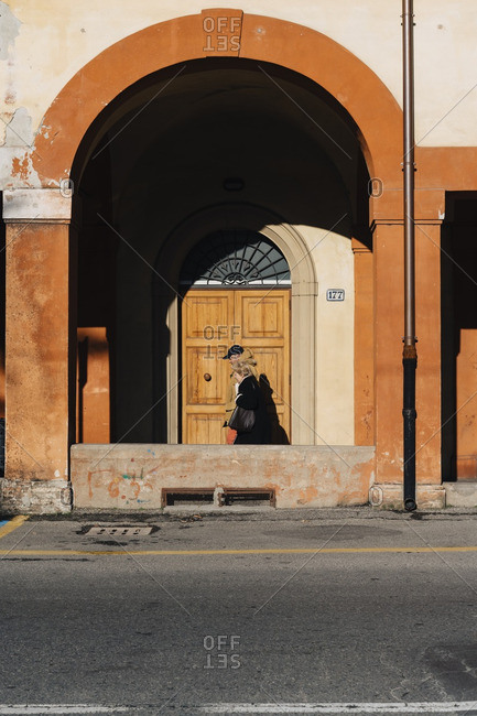 Bologna, Italy - January 4, 2017: People walking under portico