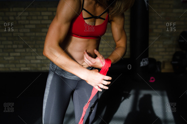 Female athlete wrapping arm in tape