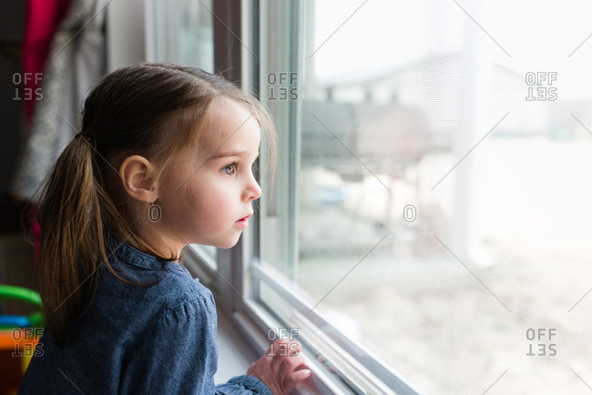 Girl gazing pensively out window