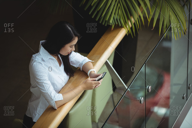 Businesswoman using mobile phone at office balcony