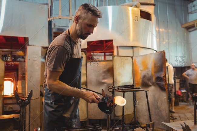 Glassblower forming and shaping a molten glass at glassblowing factory