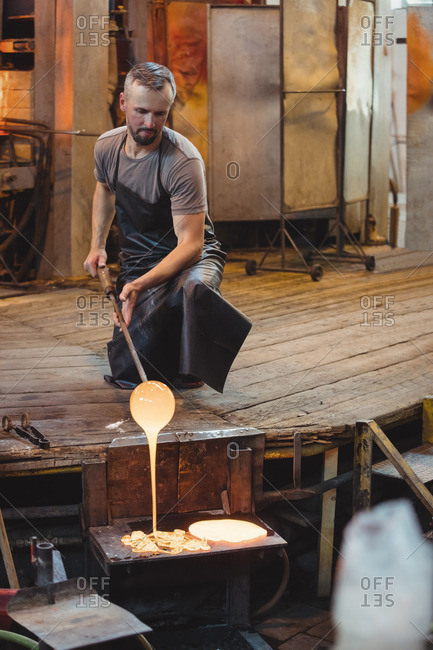 Glassblower working over a molten glass at glassblowing factory
