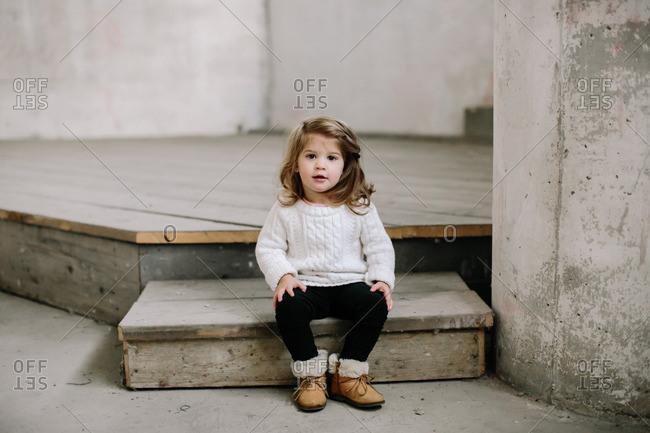 Young girl sitting on wood platform