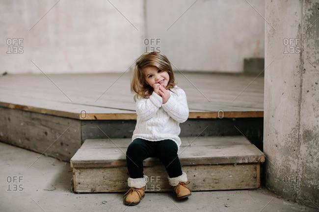 Grinning girl sitting on wood platform