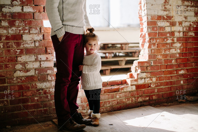 Girl by man next to broken brick wall