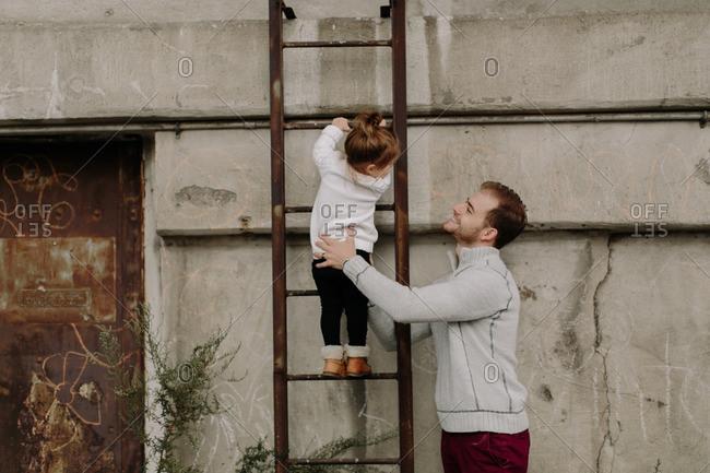 Dad helping girl climb a ladder