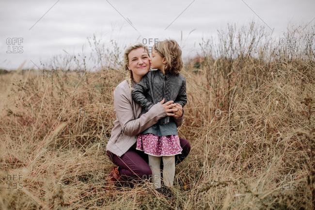 Girl kissing woman in fall field