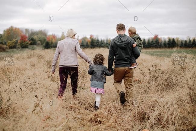 Family walking through fall field