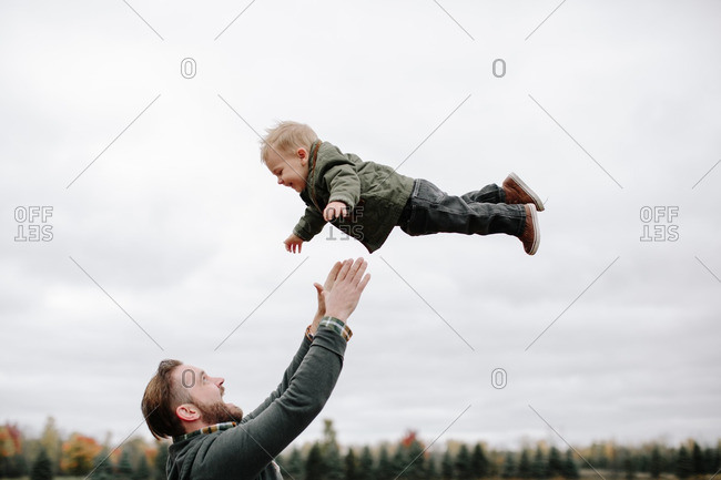Man tossing boy into the air