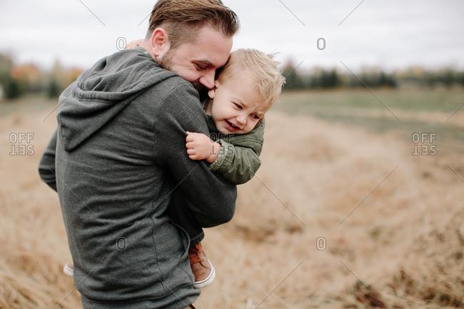 Dad cuddling boy in fall field