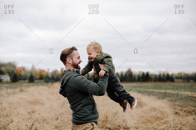 Laughing man and boy in fall field