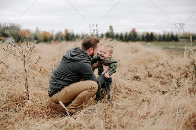 Smiling boy with dad in fall field