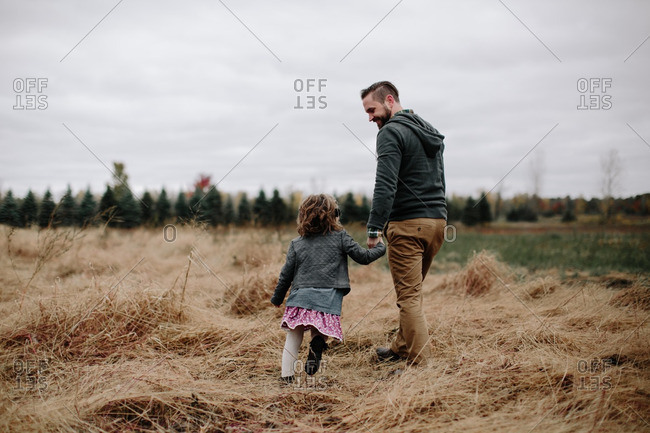 Girl walking with dad in fall field
