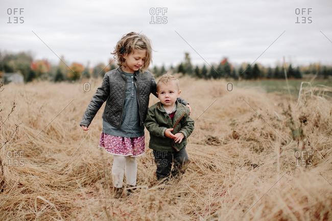 Two kids walking in fall field