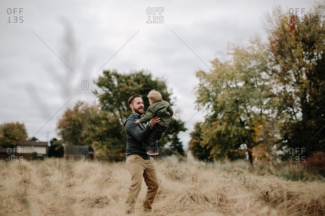 Dad playing with boy in fall field