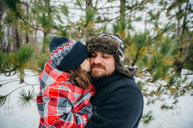 Girl kissing dad in snowy setting