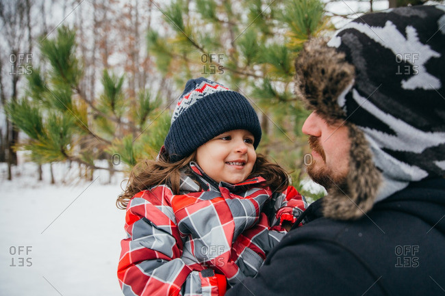 Girl smiling at man in snowy woods
