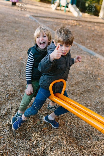 Two boys on a seesaw giving thumbs up