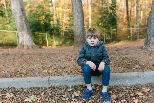 Boy sitting on a curb in the fall