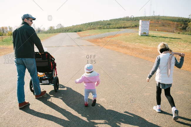 Father walking with children on a path in a park