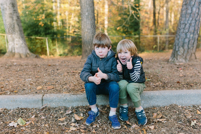 Two boys sitting on a curb in the fall