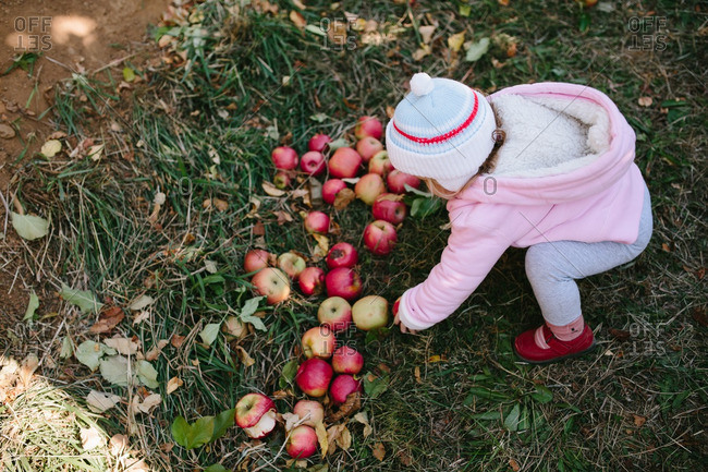 Girl picking up an apple from ground
