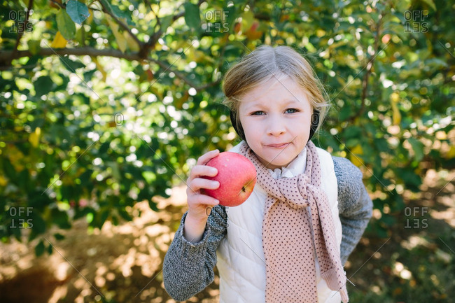 Young girl eating an apple in an orchard