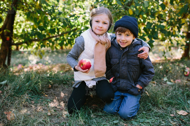 Two kids eating apples in an orchard