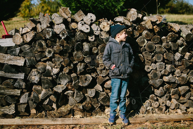 Young boy standing by stack of firewood