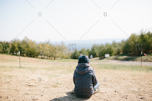 Boy sitting in a field of dirt from behind on a cold day