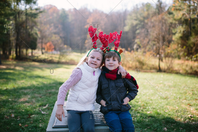 Siblings wearing reindeer antlers with arms around each other