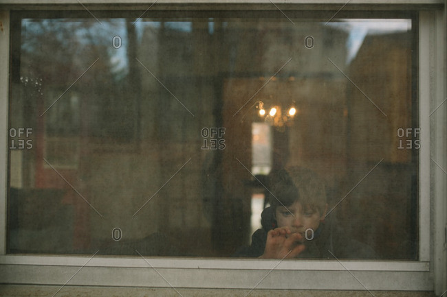 View from outside of a boy looking out of a window