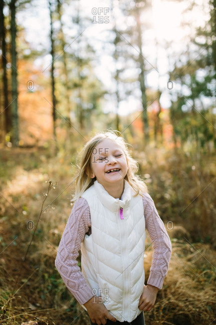 Laughing little blonde girl standing in a forest