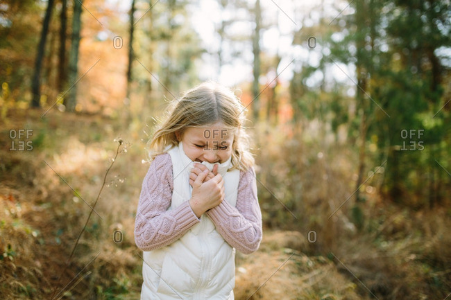 Little blonde girl laughing in a forest