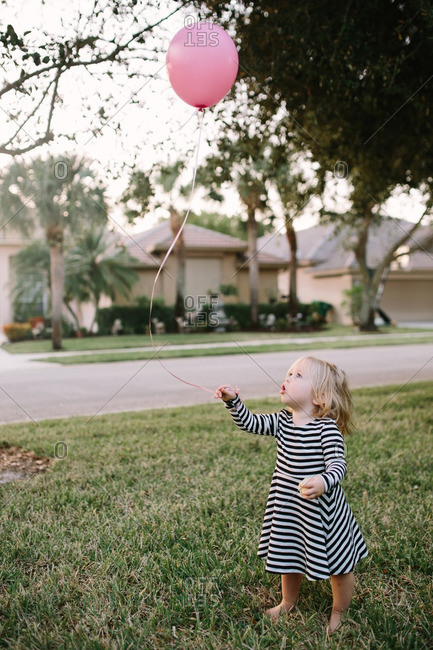 Toddler girl standing outside holding a pink balloon