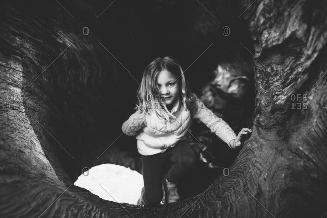 Girl playing in a hollowed out tree log