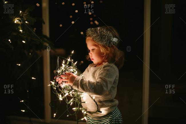 Blonde toddler girl stringing lights on a Christmas tree