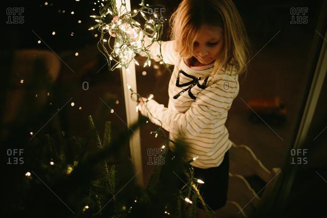 Blonde girl hanging lights on a Christmas tree
