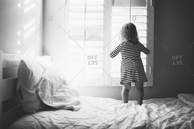 Toddler girl in a striped dress standing on a bed looking out a window