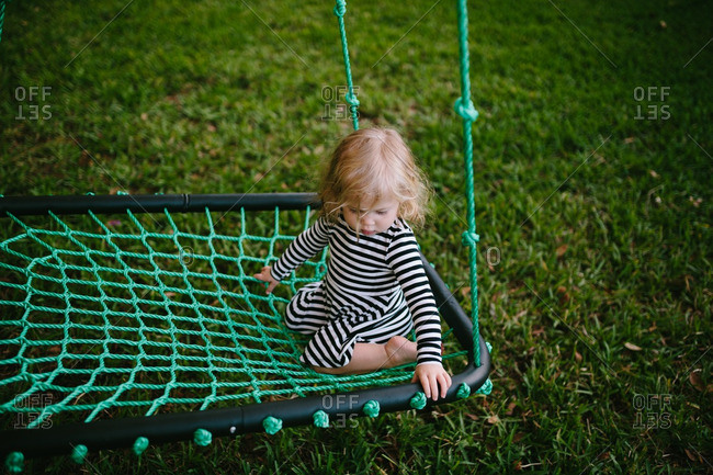 Toddler girl splaying on a netted swing
