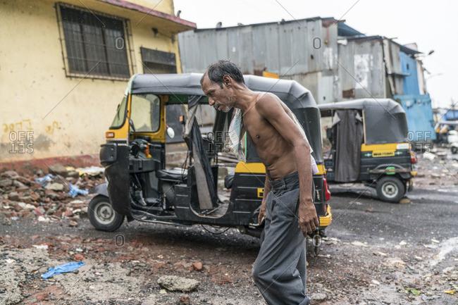 Mumbai, India - July 1, 2016: Drunken old man walking in the slums of Mumbai