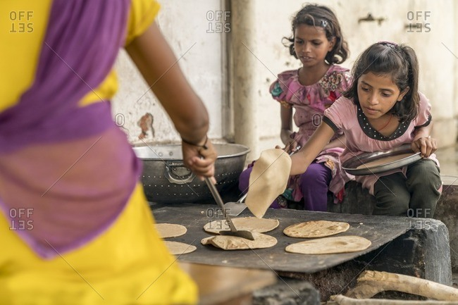 Udaipur, India - June 29, 2016: Young girls help cook bread in India