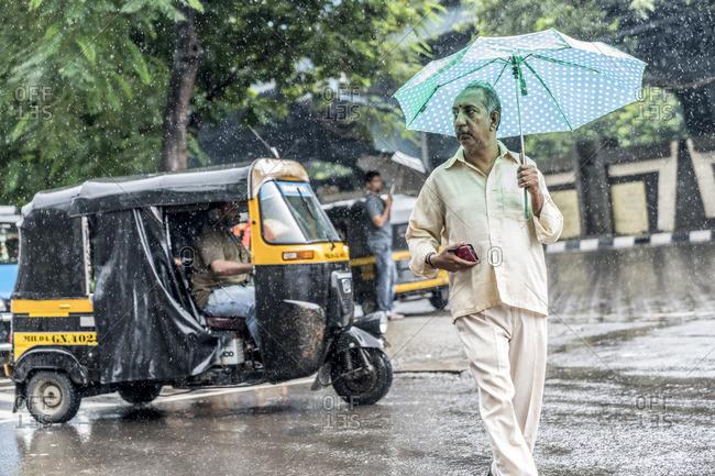 Mumbai, India - July 1, 2016: Man walking by taxi in street during a monsoon in Mumbai