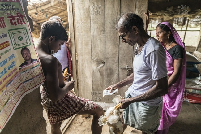 Patna, India - July 6, 2016: A small business owner with his chickens and customers in rural India