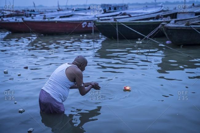 Varanasi, India - July 8, 2016: A Hindu man offers a prayer candle in the Ganges River, Varanasi