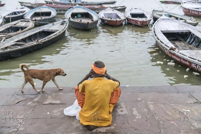 Varanasi, India - July 8, 2016: A man that sells prayer candles waiting along the Ganges River, Varanasi